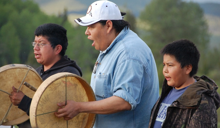Drummers two men and young boy singing outside